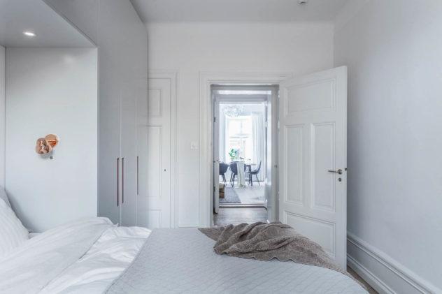 Garderobsvägg runt säng. Släta dörrar med greppet GR-1 i koppar